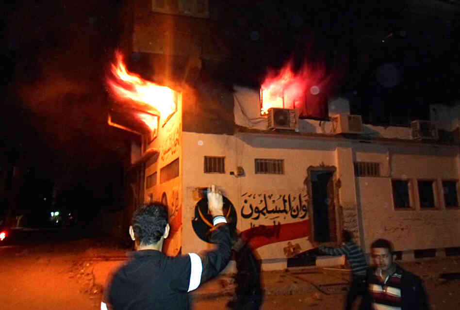 Egyptian protesters stand outside the burning office of the Muslim