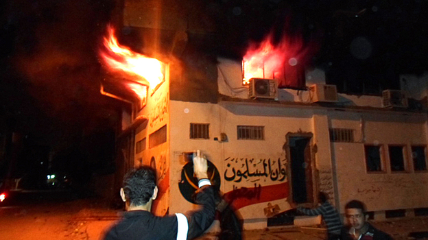Egyptian protesters stand outside the burning office of the Muslim brotherhood in Ismailia, Egypt on Wednesday. (AFP/Getty Images)