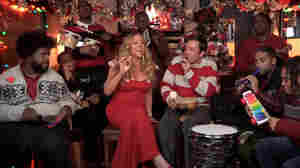"A screenshot of Jimmy Fallon and Mariah Carey performing ""All I Want For Christmas Is You"" with The Roots."