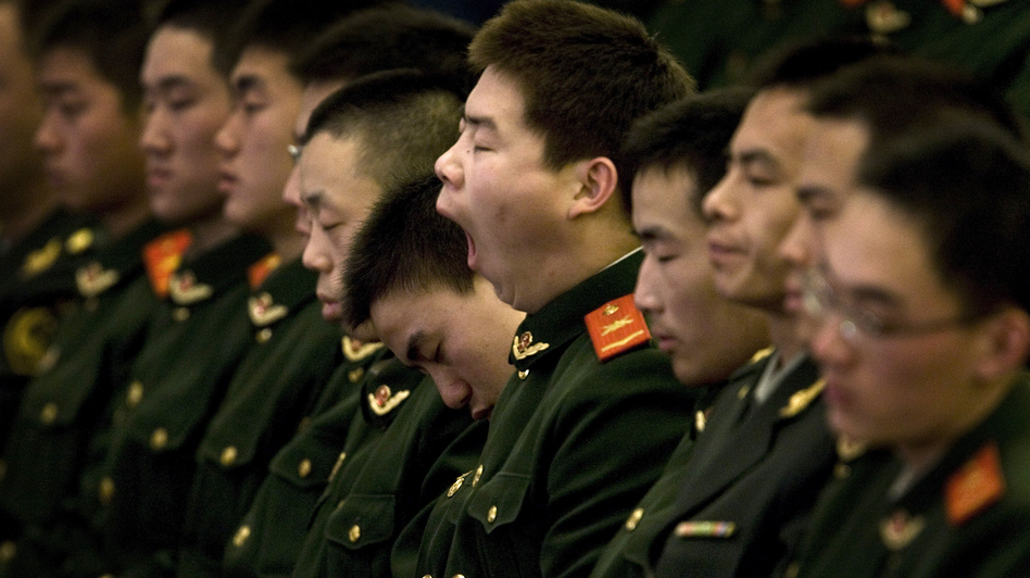 Must ... stay .... awake: A Chinese paramilitary police officer yawns and his colleagues fall asleep while then-President Hu Jintao delivers a speech at the Great Hall of the People in Beijing, China, Dec. 18, 2008. (AP)