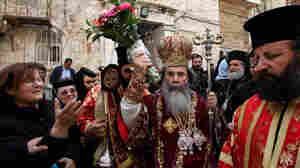 Patriarch Theophilos III, the Greek Orthodox patriarch of Jerusalem (center), splashes holy water toward worshippers after the washing of the feet ceremony in front of the Church of the Holy Sepulcher in Jerusalem in 2009, during Easter celebrations. A crisis was narrowly averted recently when the church's $2.3 million water bill was waived.
