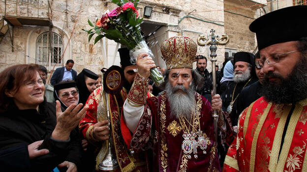 Patriarch Theophilos III, the Greek Orthodox patriarch of Jerusalem (center), splashes holy water toward worshippers after the washing of the feet ceremony in front of the Church of the Holy Sepulcher in Jerusalem in 2009, during Easter celebrations. A crisis was narrowly averted recently when the church's $2.3 million water bill was waived. (AFP/Getty Images)