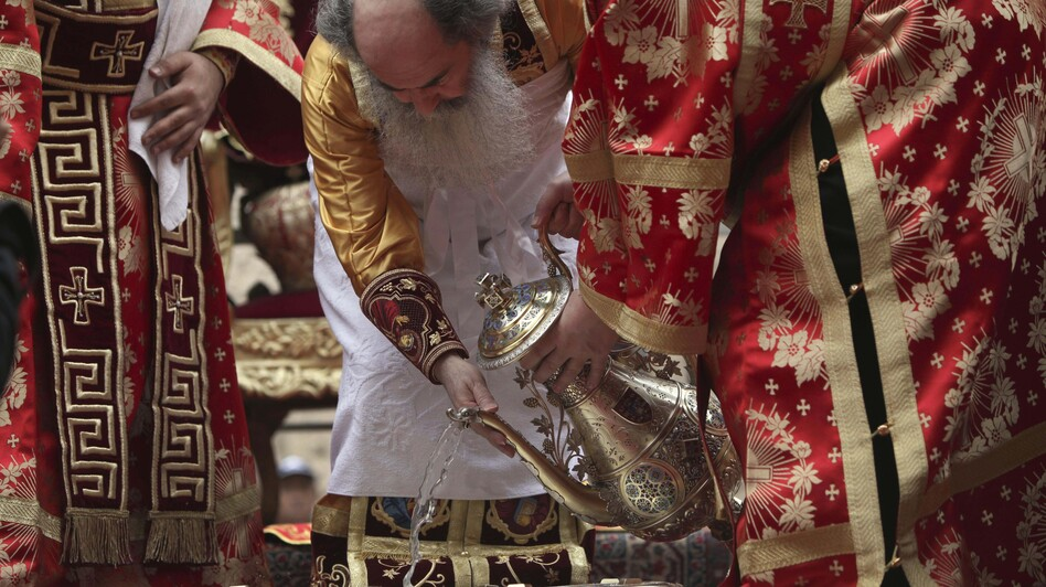 Theofilos III (center) pours water into a basin during the washing of the feet ceremony outside the Church of the Holy Sepulcher in Jerusalem's Old City in April 2011, during Easter celebrations. (AP)