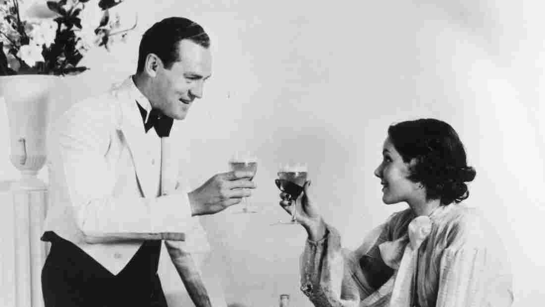 A happy-looking 1930s couple toasts.