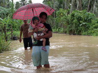A woman carries a child through a flooded road on the island of Mindanao.