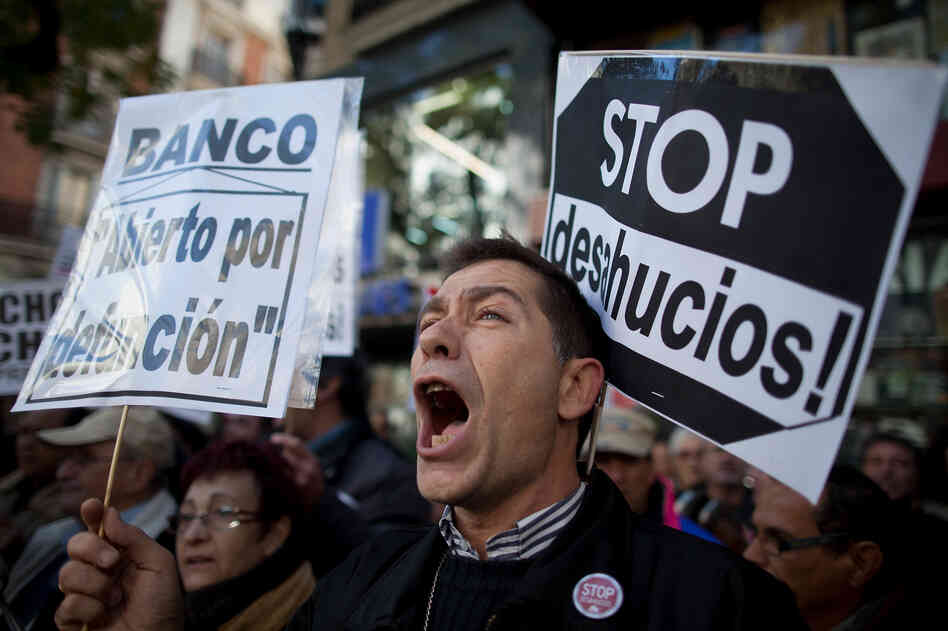 "A demonstrator shouts during a protest against housing evictions in Madrid last month. The sign to his right reads, ""Stop evictions."""