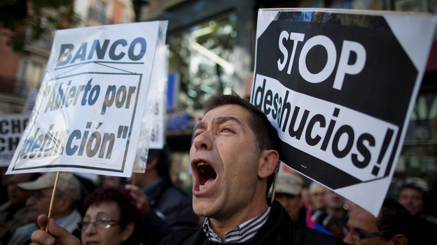 """A demonstrator shouts during a protest against housing evictions in Madrid last month. The sign to his right reads, """"Stop evictions."""" (Getty Images)"""
