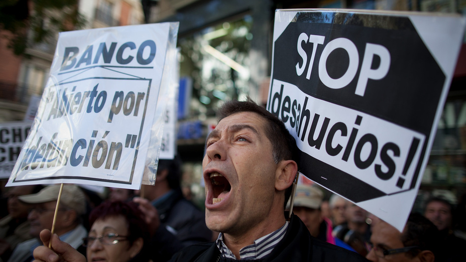 "A demonstrator shouts during a protest against housing evictions in Madrid last month. The sign to his right reads, ""Stop evictions."" (Getty Images)"