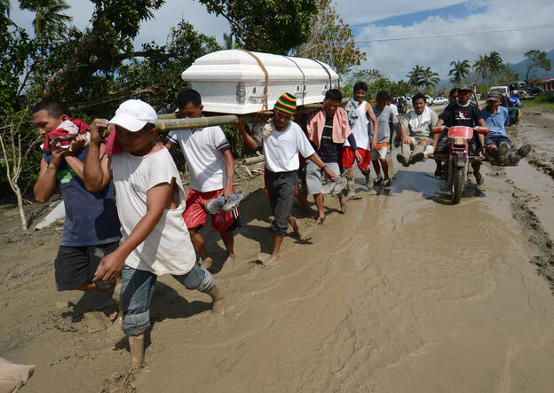 Residents carry a relative's coffin along a muddy road in the town of New Bataan, compostela province on Th