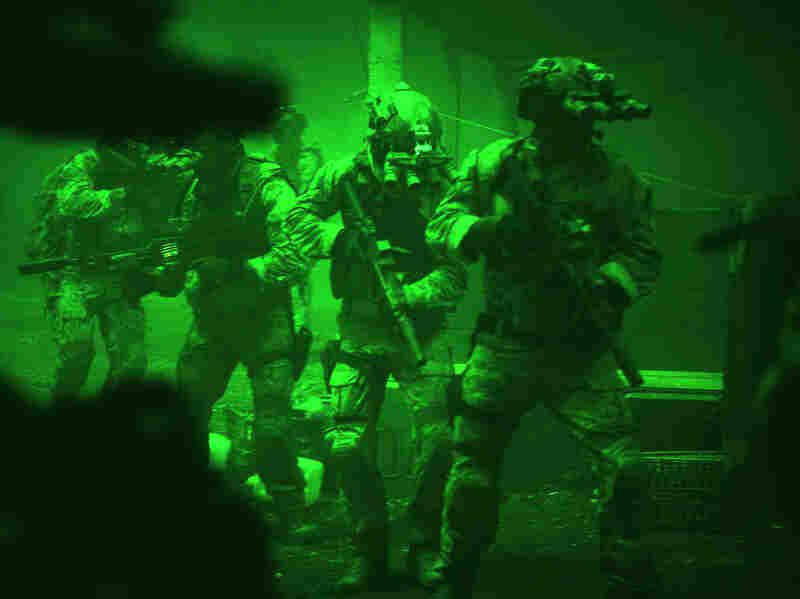 Seen through the greenish glow of night-vision goggles, Navy SEALs prepare to breach a locked door in Osama bin Laden's compound in Zero Dark Thirty.