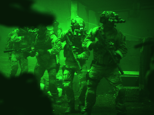 Seen through the greenish glow of night-vision goggles, Navy SEALs prepare to breach a locked door in Osama bin Laden's compound in <em>Zero Dark Thirty</em>.