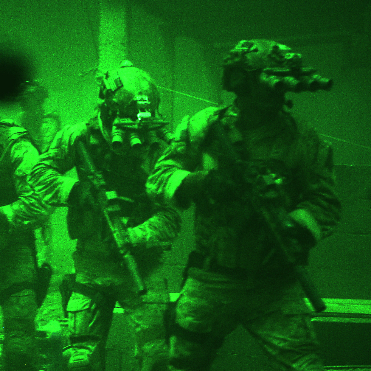 Seen through the greenish glow of night-vision goggles, Navy SEALs prepare to breach a locked door in Osama bin Laden's compound in Zero Dark Thirty.