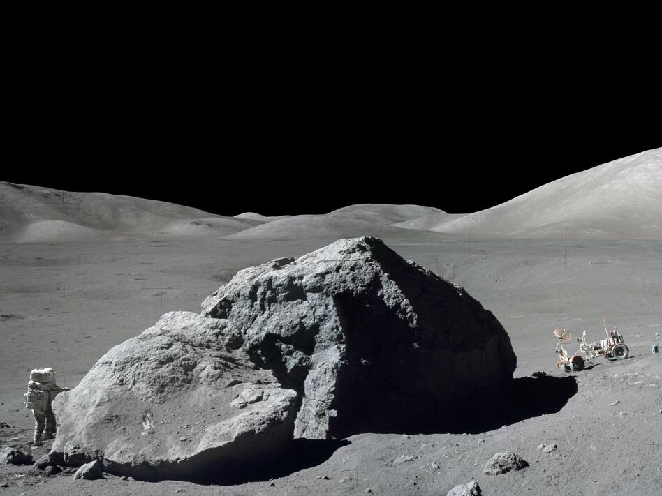 Schmitt is photographed standing next to a huge, split lunar boulder at the Taurus-Littrow landing site. The lunar roving vehicle is visible in the background. This photo is made from two frames from one of Apollo 17's cameras. (NASA)