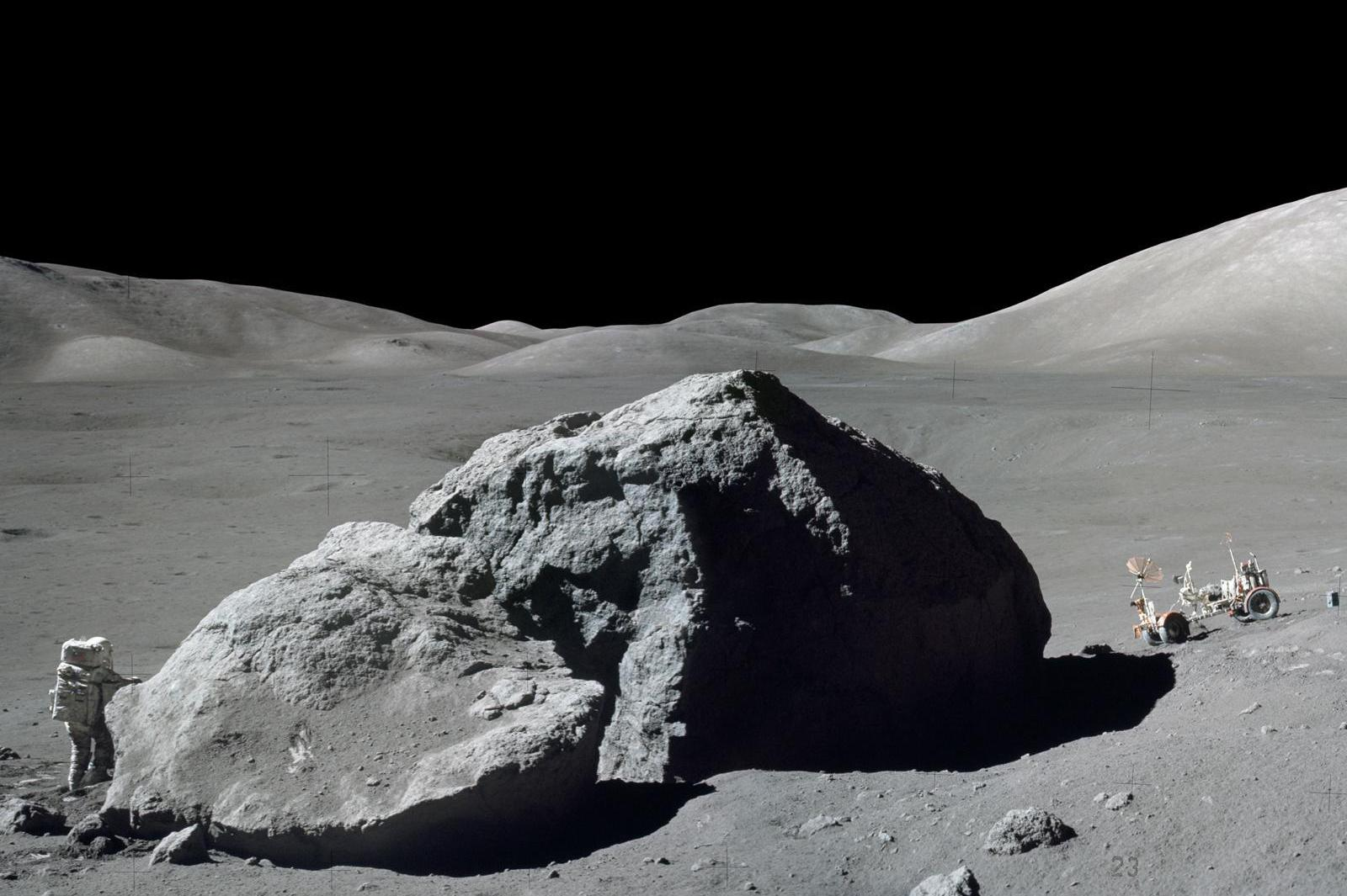Schmitt is photographed standing next to a huge, split lunar boulder at the Taurus-Littrow landing site. The lunar roving vehicle is visible in the background. This photo is made from two frames from one of Apollo 17's cameras.