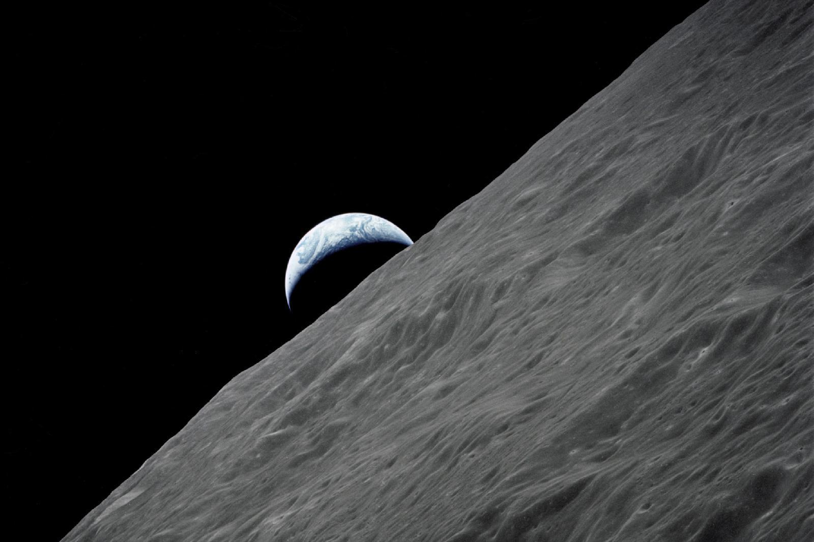 A camera aboard the Apollo 17 spacecraft captured this glimpse of Earth peeking out above the lunar horizon during the final lunar mission.