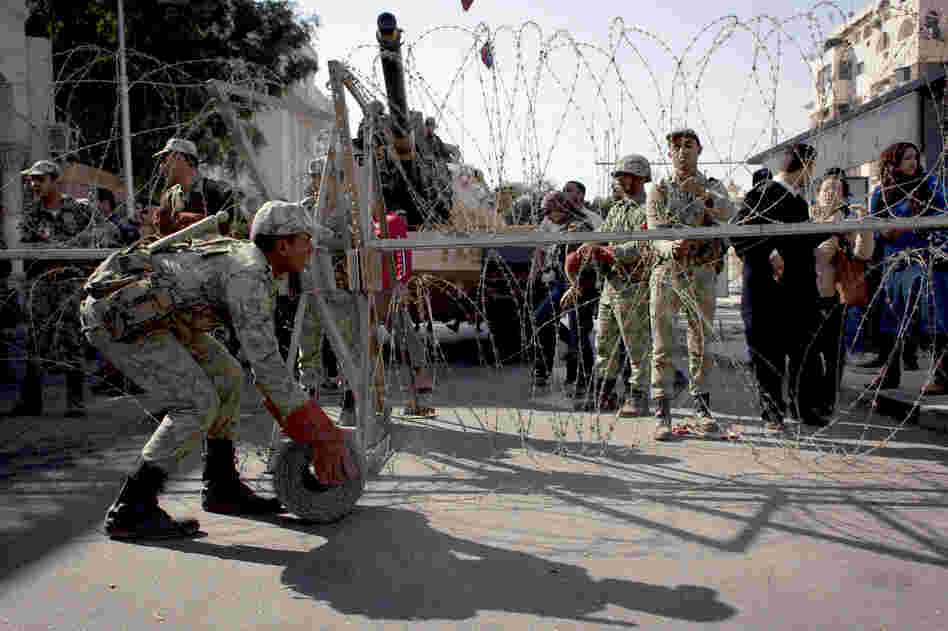 Egyptian army soldiers spread barbed wire near the presidential palace to secure the site after clashes that left several people dead and hundreds wounded.