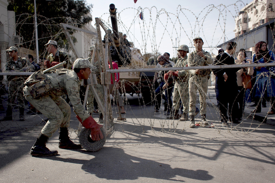 Egyptian army soldiers spread barbed wire near the presidential palace to secure the site after clashes that left several people dead and hundreds wounded. (AP)