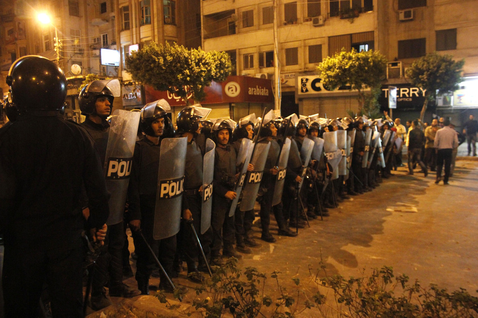 Egyptian riot police stand guard in Cairo on Wednesday during large-scale clashes that marked the worst violence of a deepening crisis over the disputed constitution. (AP)