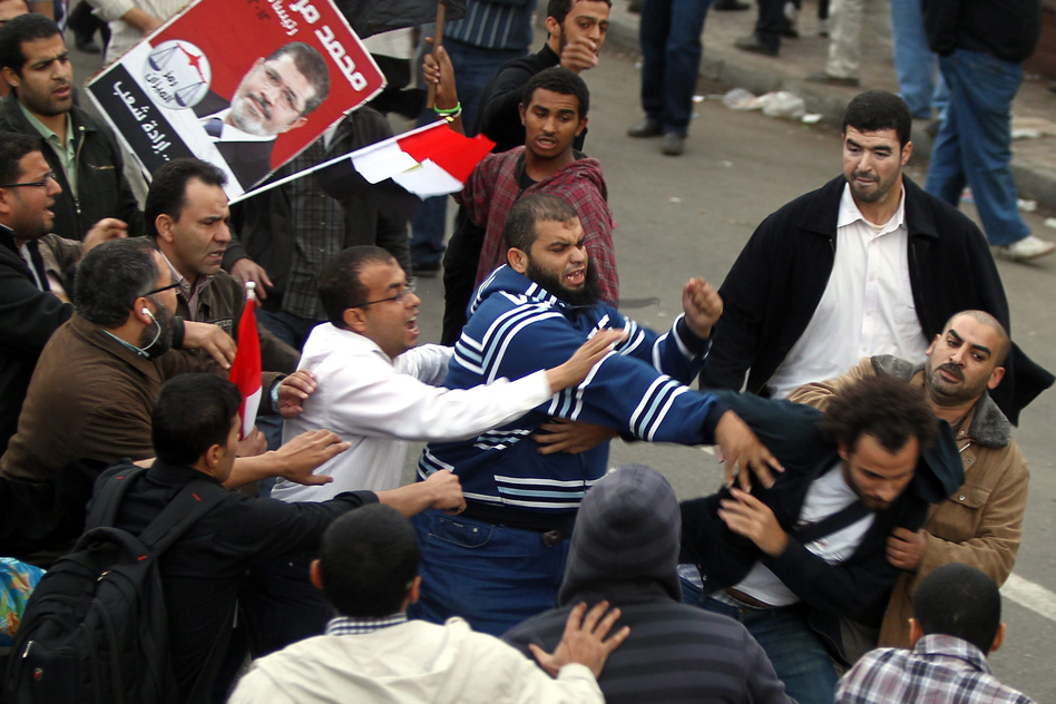 Supporters of the Muslim Brotherhood attack an opposition protester in front of the presidential palace. (EPA/Landov)