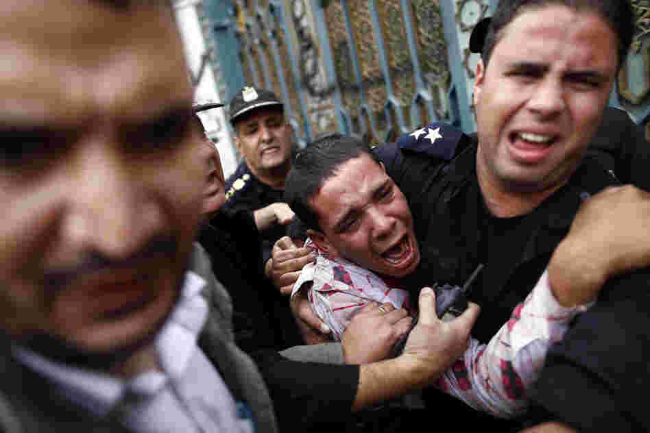 Egyptian policemen protect an opposition demonstrator after a scuffle with members of the Muslim Brotherhood outside the presidential palace in Cairo.