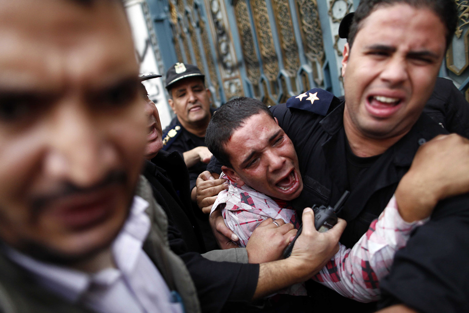 Egyptian policemen protect an opposition demonstrator after a scuffle with members of the Muslim Brotherhood outside the presidential palace in Cairo. (AFP/Getty Images)