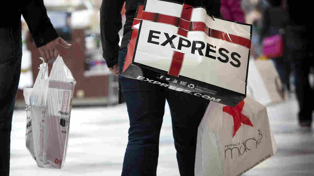 Shoppers carry bags during Black Friday sales at the South Shore Plaza in Braintree, Mass. Right now, consumers are feeling positive, but the mood among businesses is at recession levels.