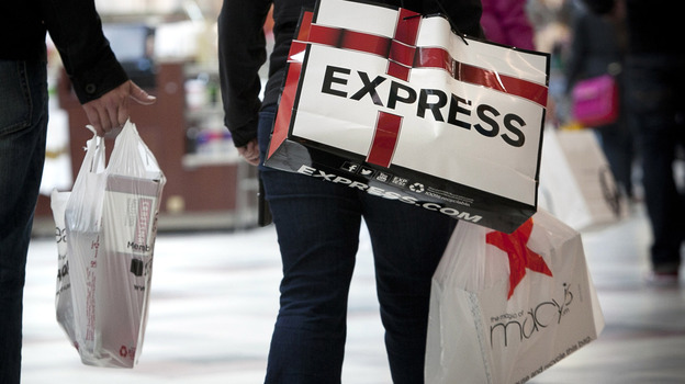 Shoppers carry bags during Black Friday sales at the South Shore Plaza in Braintree, Mass. Right now, consumers are feeling positive, but the mood among businesses is at recession levels. (Getty Images)