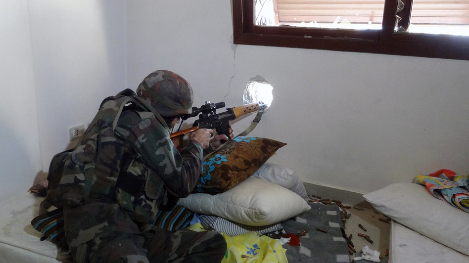A Syrian soldier aims his rifle during clashes with rebel forces in the Damascus suburb of Daraya on Sunday. Syrian soldiers have been taking over private homes and apartments, and have sometimes looted and trashed them, according to Syrian civilians. (AP/SANA)