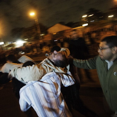 A man who had been with members of the Muslim Brotherhood and supporters of Egyptian President Mohamed Morsi when he was injured during overnight clashes in Cairo is carried from the scene by others.
