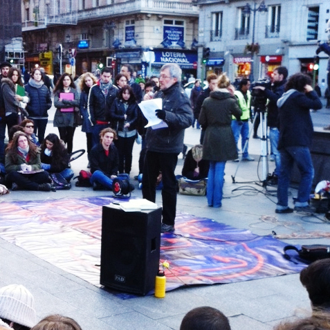 Last week in Madrid's Puerta Del Sol square, a professor teaches a lesson outdoors while students take notes, all as a means of protesting education cuts.