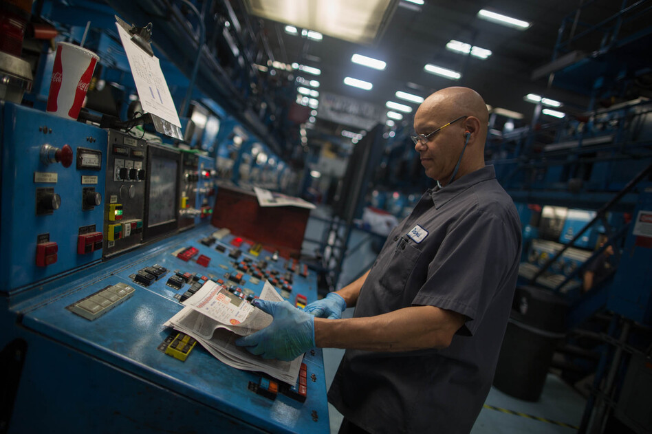 A worker inspects a copy of a paper fresh off the presses at The Orange County Register's facility in Santa Ana. (KPCC)