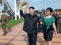 North Korean leader Kim Jong Un (center), accompanied by his wife, Ri Sol Ju, waves to the crowd as they inspect the Rungna People's Pleasure Ground in Pyongyang on July 25 in this photo released by the Korean Central News Agency. For North Koreans, it was stunning to see the first lady at the leader's side — and holding his arm.