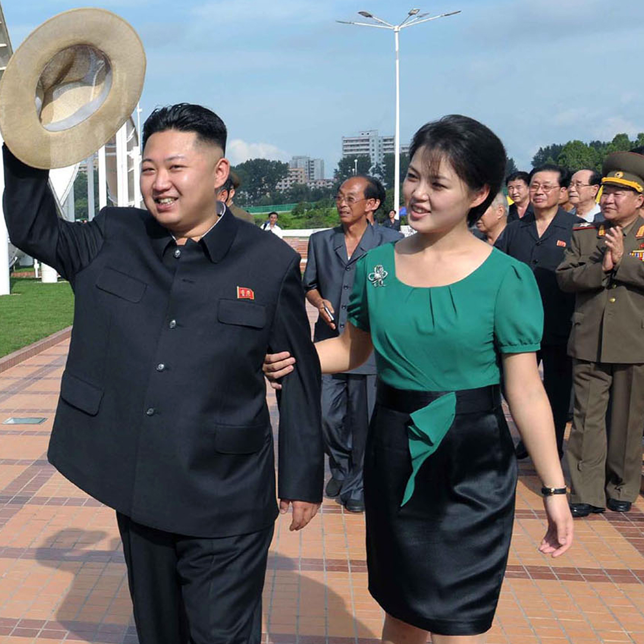 North Korean leader Kim Jong Un (center), accompanied by his wife, Ri Sol Ju, waves to the crowd as they inspect the Rungna People's Pleasure Ground in Pyongyang on July 25 in this photo released by the Korean Central News Agency. For North Koreans, it was stunning to see the first lady at the leader's side -- and holding his arm.