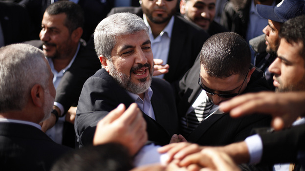 The exiled Hamas chief Khaled Mashaal shakes hands with supporters upon his arrival at Rafah crossing in the southern Gaza Strip. (AP)