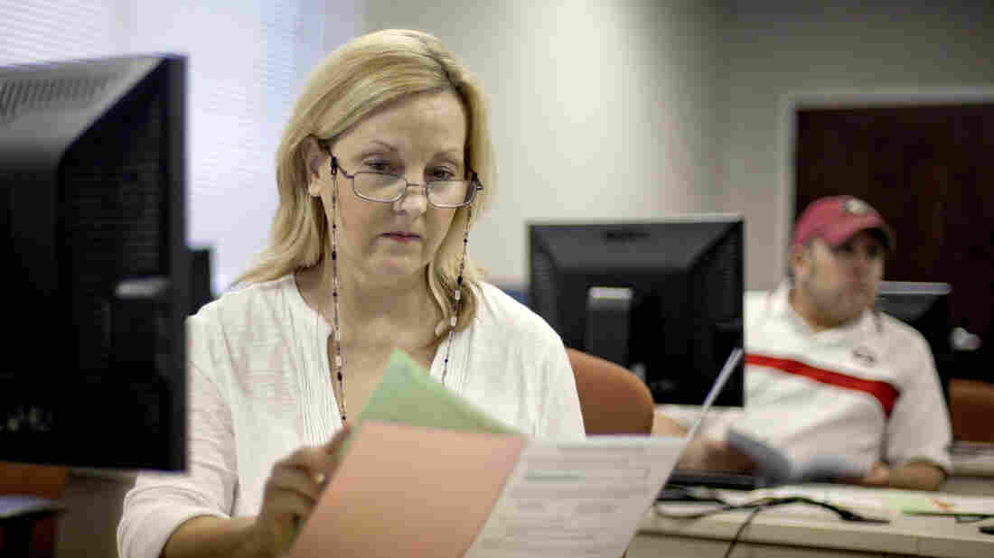 Judy Smith, of Dalton, Ga., looks over paperwork as she files for unemployment benefits in August after being laid off from a catering job. More than 2 million people who get extended benefits may lose them if Congress doesn't act soon.