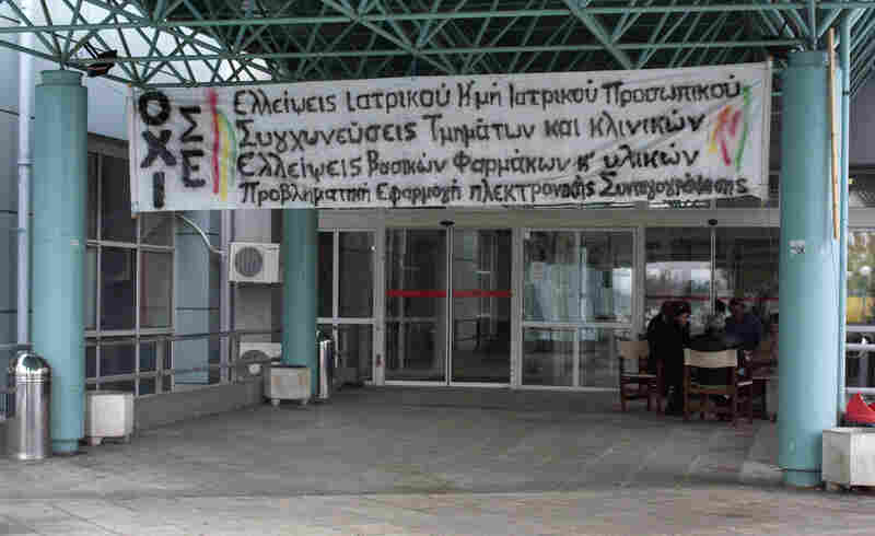 A hand-painted banner decrying drastic cuts to the health care budget is draped on the main entrance of the Regional Hospital of Serres in northern Greece.