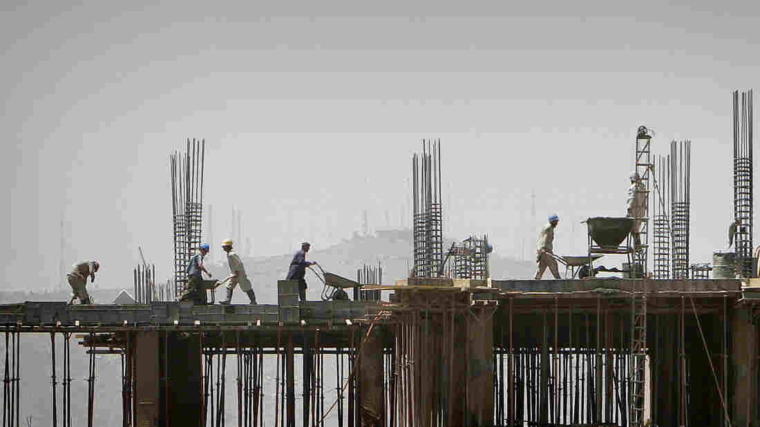 Laborers work on a building in Kabul, Afghanistan. Following the drawdown of U.S. troops and NGOs, many construction companies are without projects and being forced to close offices and downsize.