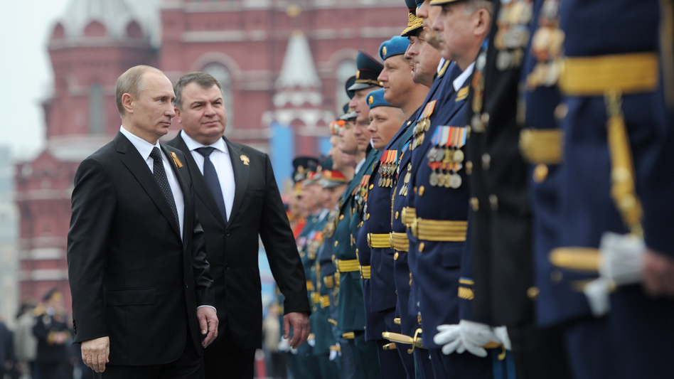 Russian President Vladimir Putin and former Defense Minister Anatoly Serdyukov, who was recently fired, review military officers on Moscow's Red Square in May. Putin's decision to sack Serdyukov has touched off widespread speculation on the motive. (AP)