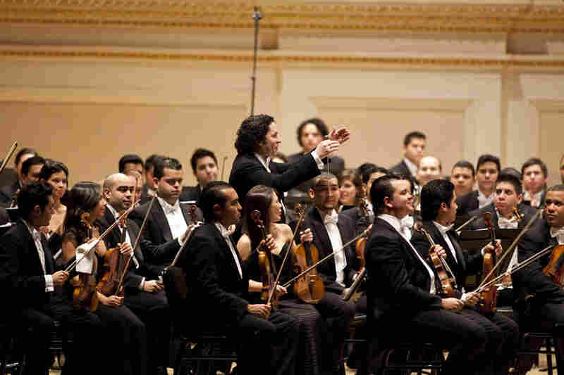 Gustavo Dudamel wades through the orchestra just before the start of the Carnegie Hall concert.