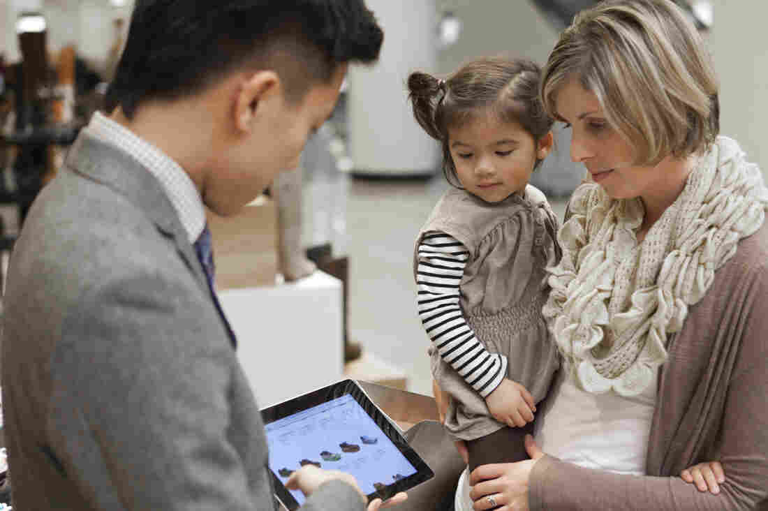 A Nordstrom salesperson shows a customer an online selection of shoes on an in-store iPad. Like some other retailers, Nordstrom is using mobile devices to make on-the-spot sales and check companywide product inventory instantly.