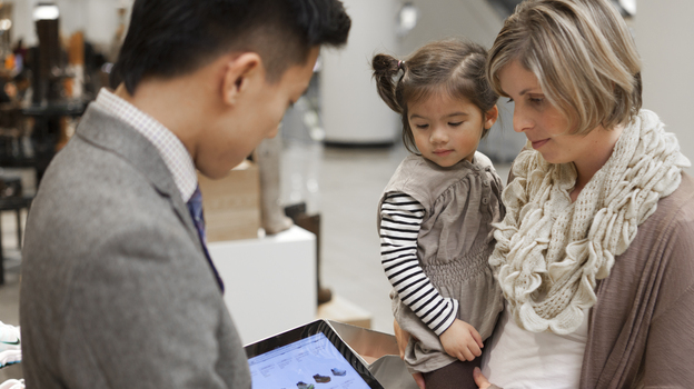 A Nordstrom salesperson shows a customer an online selection of shoes on an in-store iPad. Like some other retailers, Nordstrom is using mobile devices to make on-the-spot sales and check companywide product inventory instantly. (Courtesy of Nordstrom)