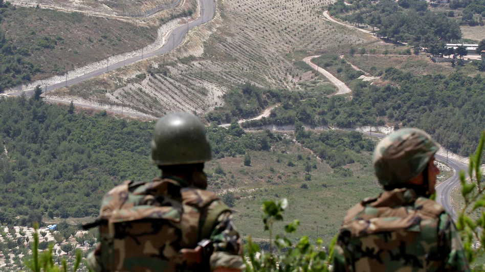 In this June 2011 photo, Syrian soldiers look down on the village of Khirbet al-Joz, on the border with Turkey. Syrian rebels recently captured the village, and residents are setting up a secular, democratic leadership they hope will serve as a model. (AFP/Getty Images)