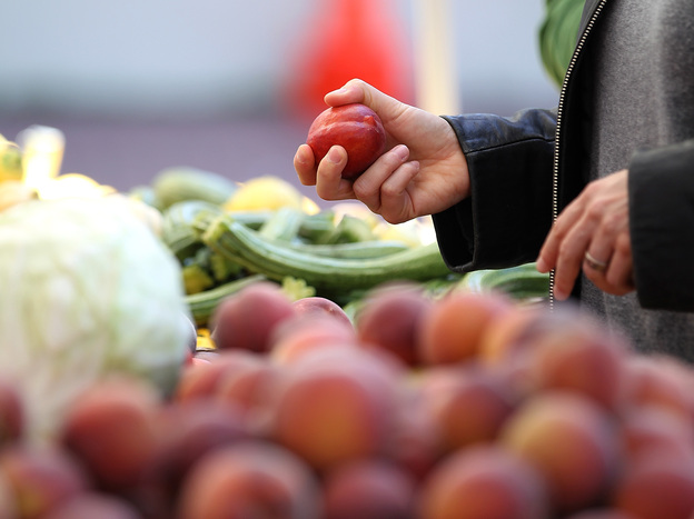 A customer shops for nectarines at a farmers market in San Francisco.