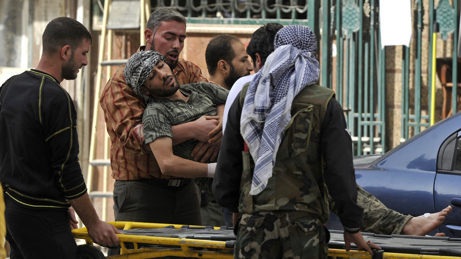 Syrians lift a wounded rebel fighter to take him into a hospital in Aleppo, Syria, in October. Doctors have few supplies to treat wounded fighters in Syria. (AFP/Getty Images)