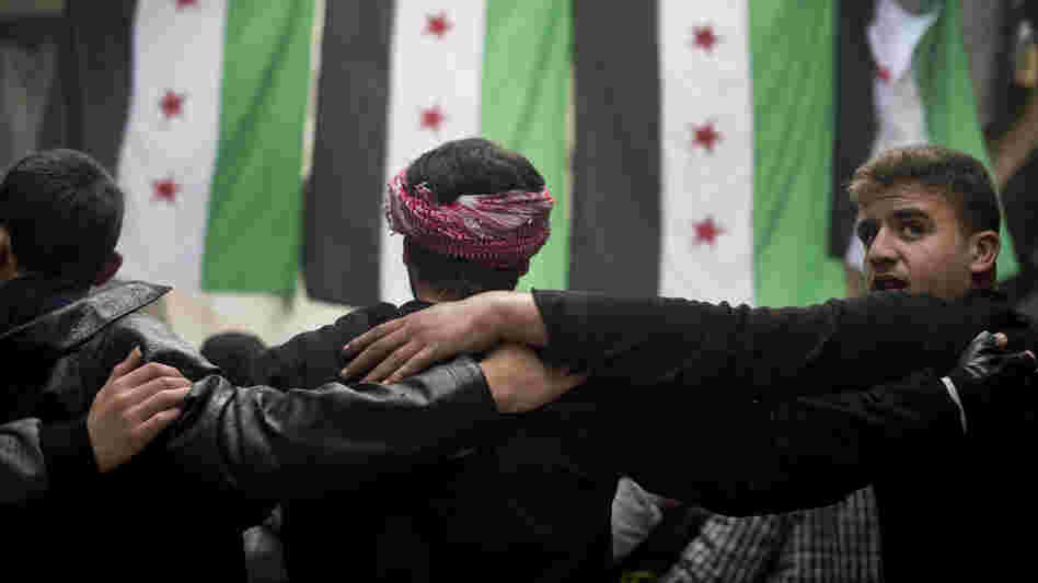 Rebel fighters take part in a demonstration against the Syrian regime after Friday prayers in Aleppo on Friday.
