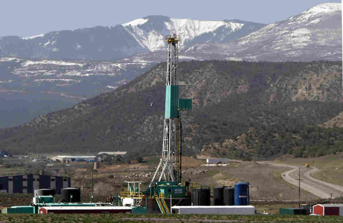 FILE - In this April 22, 2008 file photo, a natural gas well pad sits in front of the Roan Plateau near Rifle, Co. The director of the Colorado Oil and Gas Conservation Commission, David Neslin, said Monday, Dec. 5, 2011, that requiring drilling companies to publicly disclose what chemicals they use in hydraulic fracturing is only one tool for protecting public health and the environment.