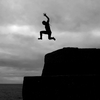 A boy jumps into the sea from high above in the harbor of Mousehole, Cornwall, England.