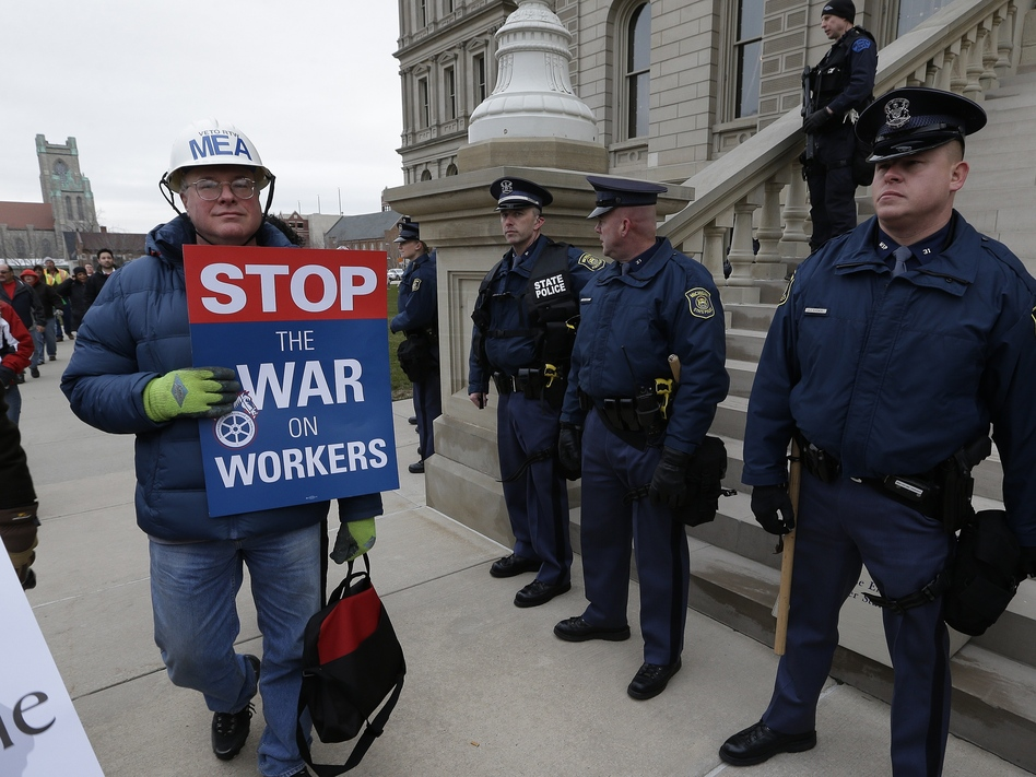 A right-to-work protester walks past Michigan state police at the capitol in Lansing on Tuesday. The Michigan Legislature is expected to pass legislation Tuesday that would bar contracts requiring employees to pay union dues as a condition of employment.