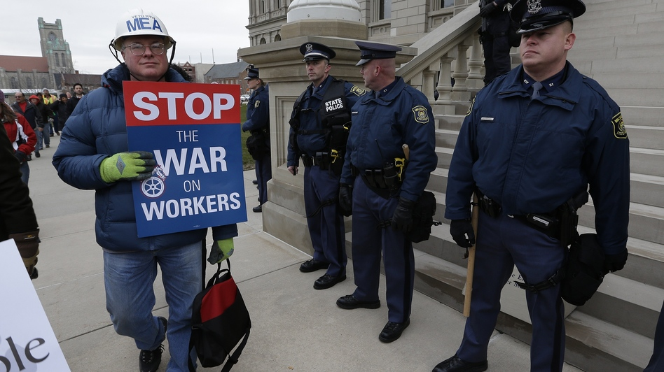 A right-to-work protester walks past Michigan state police at the capitol in Lansing on Tuesday. The Michigan Legislature is expected to pass legislation Tuesday that would bar contracts requiring employees to pay union dues as a condition of employment. (AP)