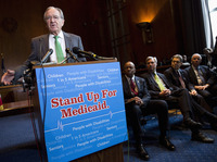 Sen. Tom Harkin, D-Iowa, speaks Tuesday as Rep. Elijah Cummings, D-Md., Sen. Sheldon Whitehouse, D-R.I., Sen. Al Franken, D-Minn., and Sen. Ben Cardin, D-Md., listen during a news conference on Capitol Hill calling for no reduction in the Medicare and Medicaid budgets as part of the year-end budget talks.
